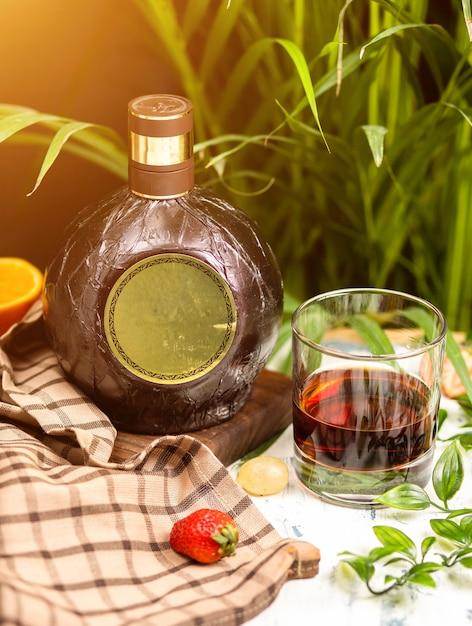 Рюмка и традиционная круглая бутылка на деревянной доске на кухонном столе. с проверкой скатерть, фрукты и травы вокруг. Бесплатные Фотографии