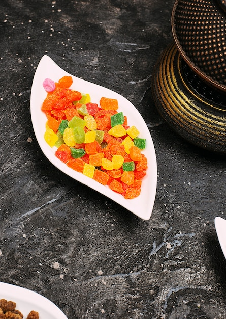 黒いテーブルの上の皿に甘い色のゼリージューシーマーマレードがたくさん 無料写真