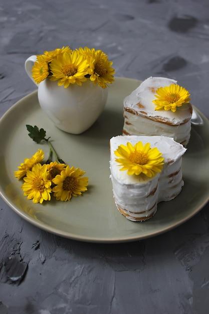 Два медовых торта в форме сердца с декором из желтых цветов на керамической тарелке Бесплатные Фотографии