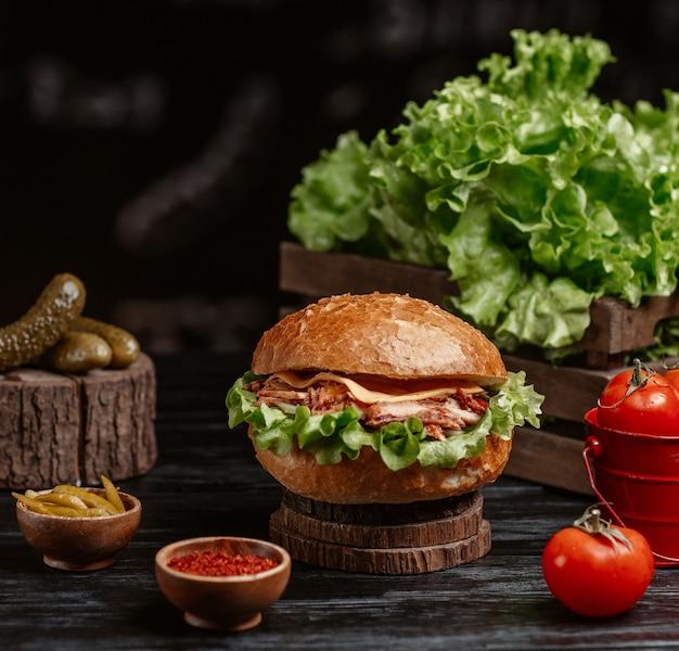 素朴なテーブルでトゥルシュとスマフを添えたハンバーガー 無料写真
