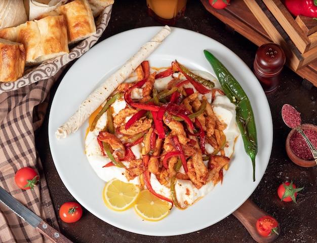 チキン・ファヒータ、チキンの切り身、白い皿にパンのスライスとラバッシュのピーマン炒め 無料写真