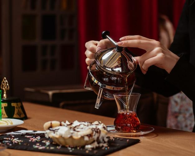 お菓子とお茶のテーブルにお茶を入れて女性 無料写真