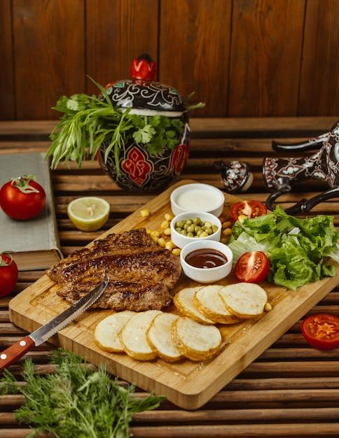 木製のテーブル、サイドビュー、グリーンサラダ、豆、マヨネーズの丸いローストポテトのビーフステーキ 無料写真