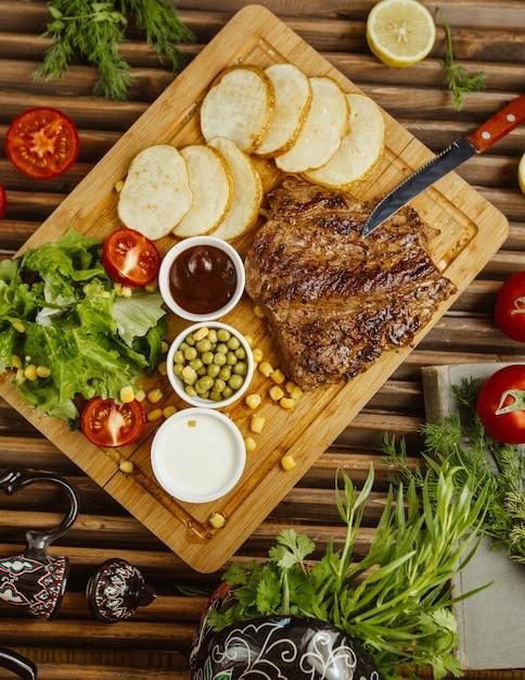 木製テーブルの上に丸いローストポテトを添えたビーフステーキ、グリーンサラダ、豆、マヨネーズ添え 無料写真