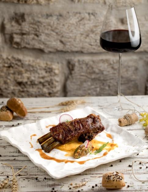 白いプレートに赤ワインのグラスとソースのビーフステーキ。 無料写真