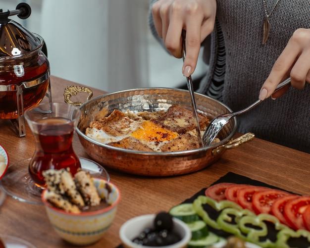 Женщина ест завтрак омлет внутри сковороды, вокруг стола, пожертвованного с оливками, овощами и черным чаем. Бесплатные Фотографии