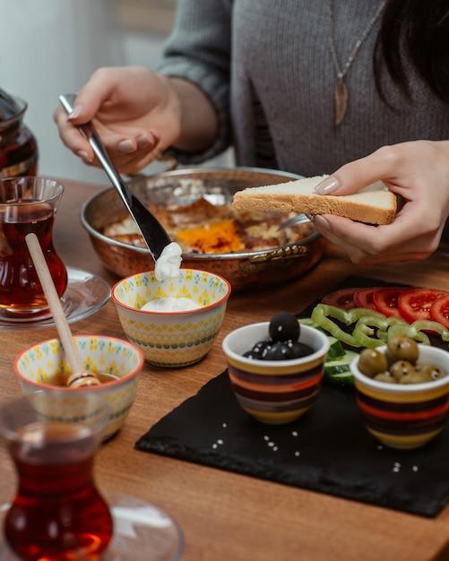 たくさんの食べ物がある朝食用テーブルの周りのパンのスライスにクリームを置く女性。 無料写真