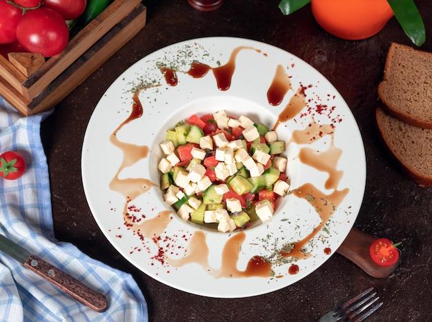 野菜、トマト、きゅうり、ロカサラダ。スマークとレモンの白い皿の中の台所のテーブルの上のサラダ 無料写真