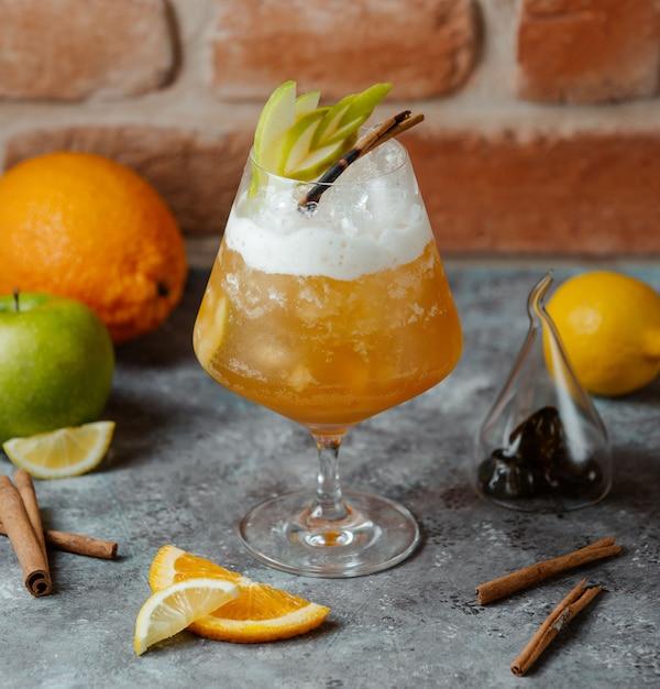 アイスキューブと中にリンゴのスライスを入れたレモンとオレンジジュースの冷たい飲み物 無料写真