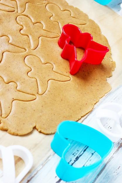 ジンジャーブレッドマンクッキーを扱うプロセスは、白い木製のテーブルにカラフルなクッキーカッターの周りの紙を焼くのに赤いジンジャーブレッドマン型切断ジンジャーブレッド生地を使用します。上面図 無料写真