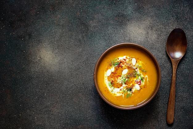 ローストしたカボチャとニンジンのスープ、クリーム、種子、新緑のセラミックボウル。上面図 無料写真