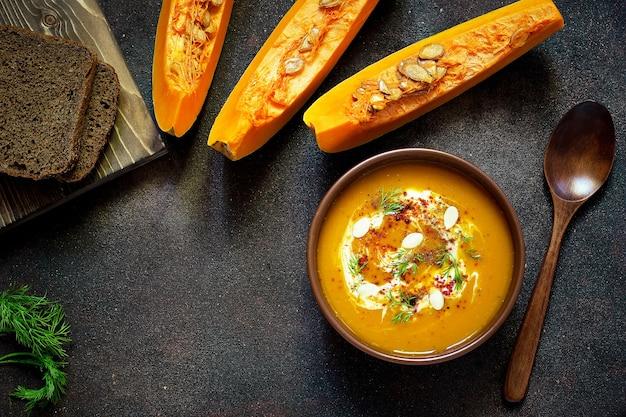 Жареный суп из тыквы и моркови со сливками, семенами и свежей зеленью в керамической миске. вид сверху Бесплатные Фотографии