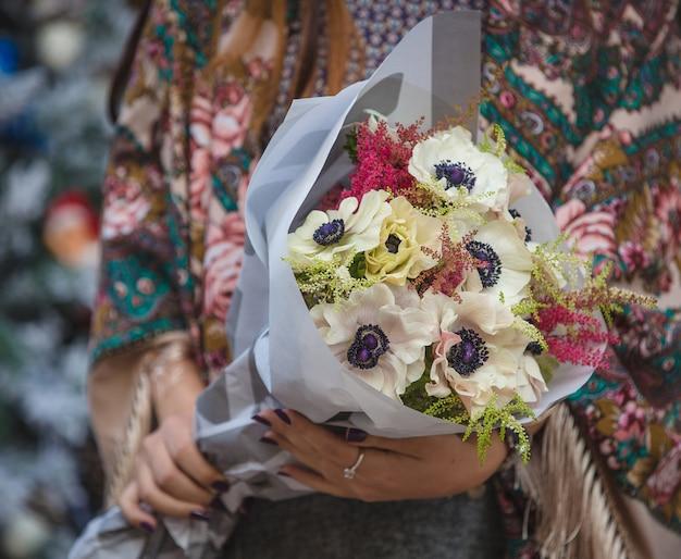 ソーホーショールの女性の手に白いヒマワリの花束 無料写真