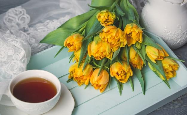 黄色いチューリップの束が付いている紅茶のカップ 無料写真
