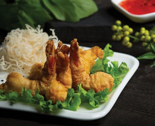 Жареные куриные ножки подаются с рисовыми спагетти и зеленым салатом в белой тарелке Бесплатные Фотографии