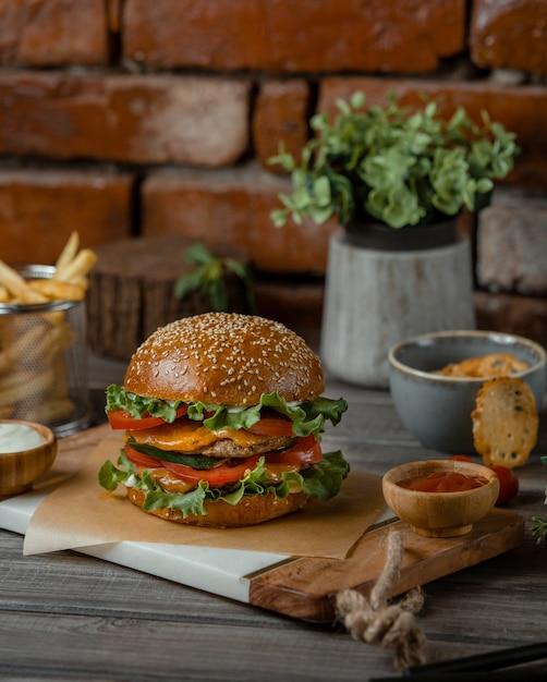素朴なテーブルの上に溶けたチェダーチーズとスマフを添えたハンバーガー 無料写真