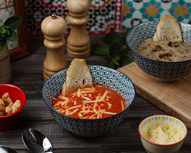 新鮮なトマトのスープ、細かく刻んだパルメザンチーズと青いボウルにパンのスライス 無料写真