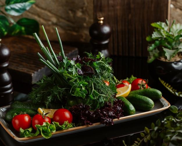 Тарелка свежих сезонных овощей, включая помидоры, огурцы и зелень Бесплатные Фотографии