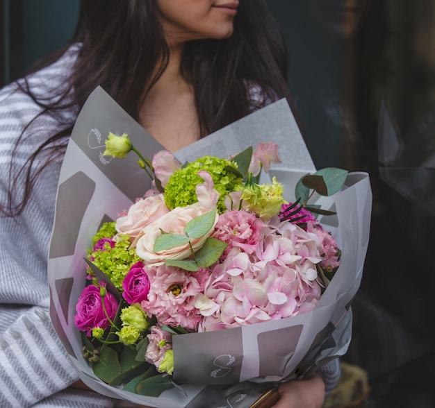 季節の花の花束を持って部屋に座っている女性 無料写真