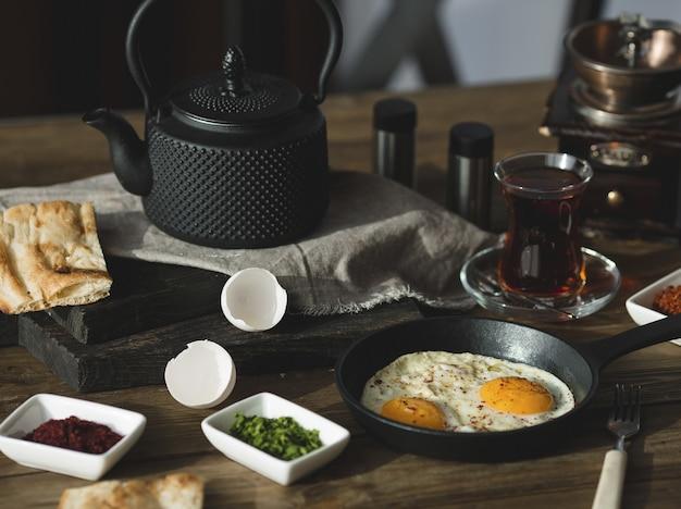 目玉焼き、ハーブ、紅茶のガラスの朝食用テーブル 無料写真