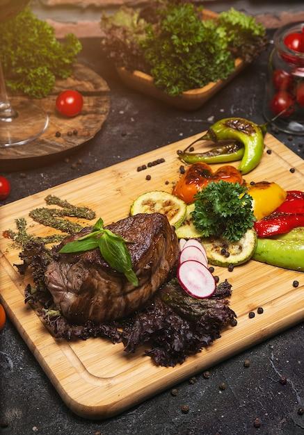 クラブビーフステーキペッパーソースとまな板の上の野菜のグリル 無料写真