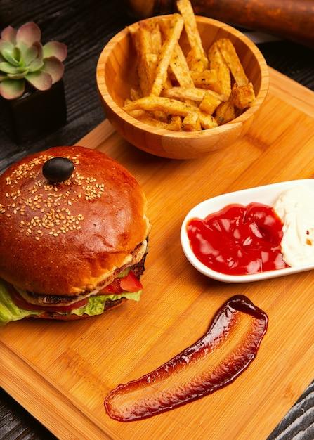 Бургер из куриного мяса с ломтиками помидоров и листьями салата, подается с картофелем фри, кетчупом и майонезом на деревянной доске Бесплатные Фотографии