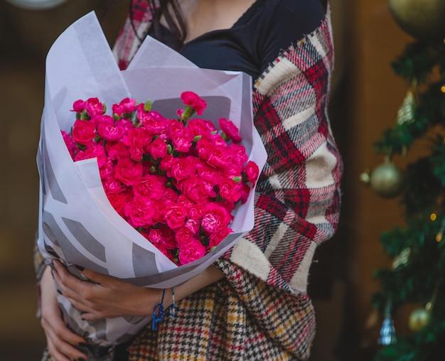 カーネーションのピンクの花束を持って肩にショールを持つ女性 無料写真