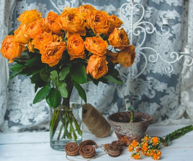 水と瓶の中のオレンジ色のバラ 無料写真