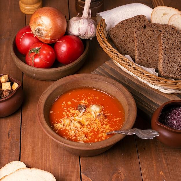 パルメザンチーズと黒小麦パンのクラッカーとトマトのスープ。 無料写真