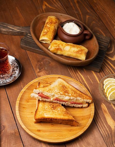 サラミ、ベーコン、ブリチクのクラブサンドイッチ、ヨーグルトと紅茶の木の板 無料写真
