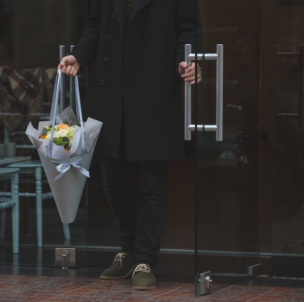 花の白い花束と入ってくる黒服を着た男 無料写真