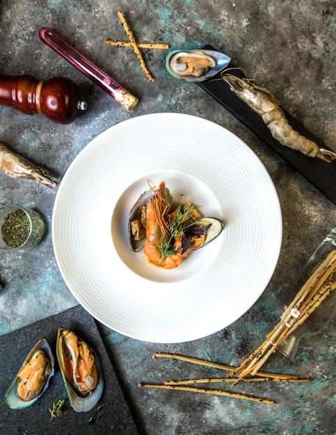 白いプレートにガレッタとシーフードムール貝のサラダ。 無料写真
