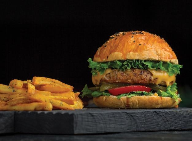 大きなマックのハンバーガーとポテトは、暗い木の板に貼り付けます。 無料写真
