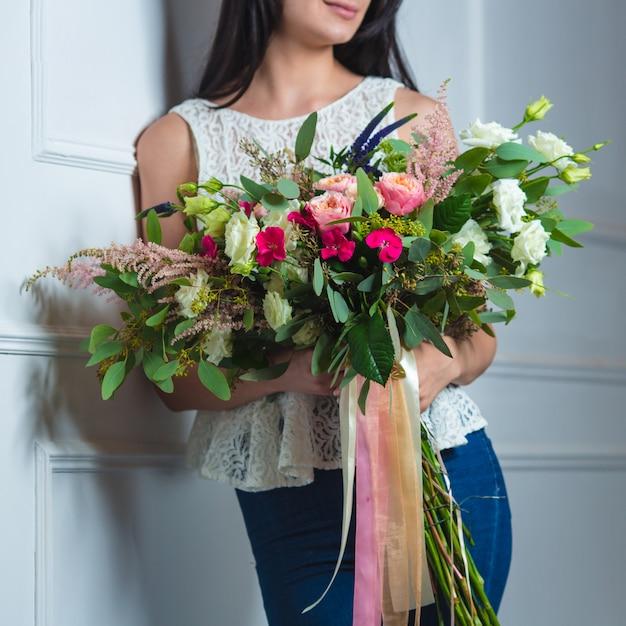 チュールリボンと大きな混合花束を持つ女性。 無料写真
