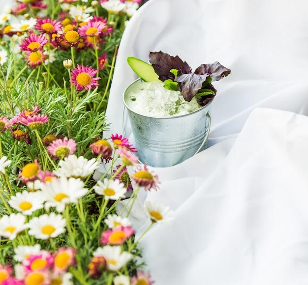 Трава с цветами, скатерть для пикника и стакан кефира с зеленью. Бесплатные Фотографии