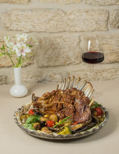 地元の牛肉ケバブとサバラン赤ワイン。 無料写真