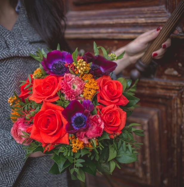 赤と紫の花の花束でドアを開ける少女。 無料写真