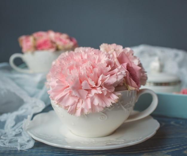 白いカップの上にピンクの花を置きます。 無料写真