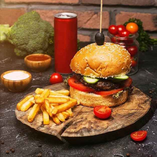 Домашний гамбургер макро с говядиной, помидорами, листьями салата, сыром и картофелем на разделочной доске. быстрое питание Бесплатные Фотографии