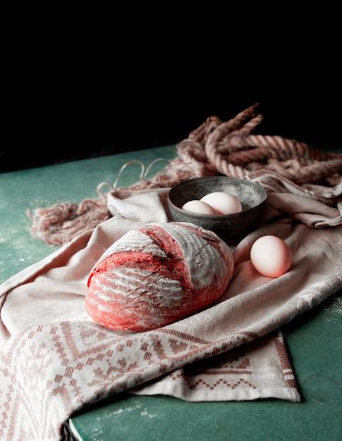 白いタオルの上に自家製のパンと、上に小麦粉を乗せた卵ボウル。 無料写真