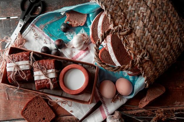 白い紙と糸で包んだパンのスライス、ボックの中のミルクポット、バスケットの周り。上面図。 無料写真