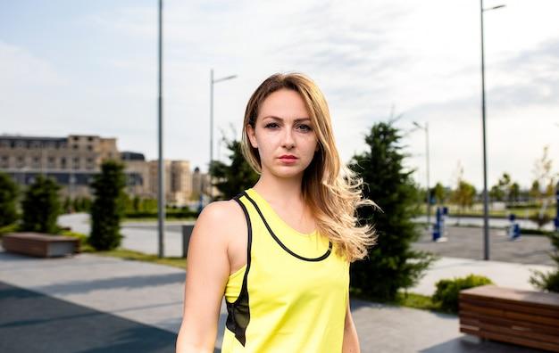 公園で黄色の衣装でスポーツの女性。 無料写真
