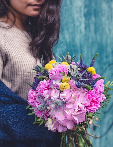 混合花の花束とベージュのセーターの女性。 無料写真