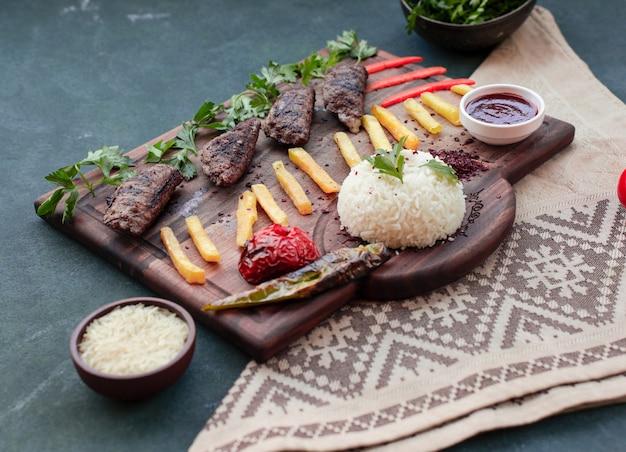 ビーフケバブ、フライドポテトスティック、グリル料理、ライスガーニッシュ、木製ボード上のソース。 無料写真