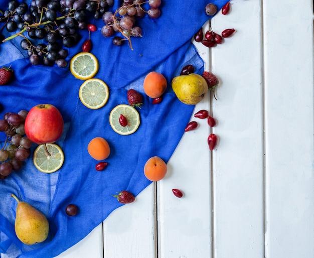 白いテーブルの上の青いリボンのミックスフルーツ。 無料写真
