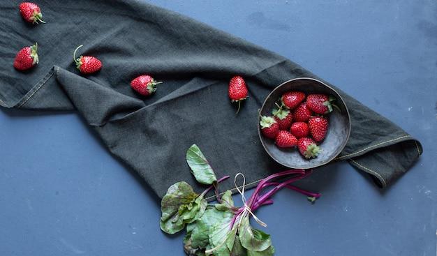 ボウルの中のイチゴと黒いマットの上の葉。 無料写真