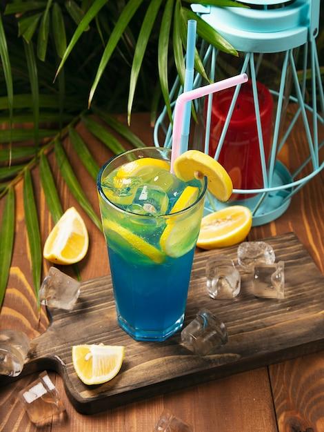 お祝いバーのカウンターで石灰で飾られた青いラグーンカクテルのクローズアップガラス。 無料写真