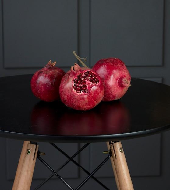 木製のスタンドと黒いテーブルの上の赤い季節の大きなザクロ 無料写真