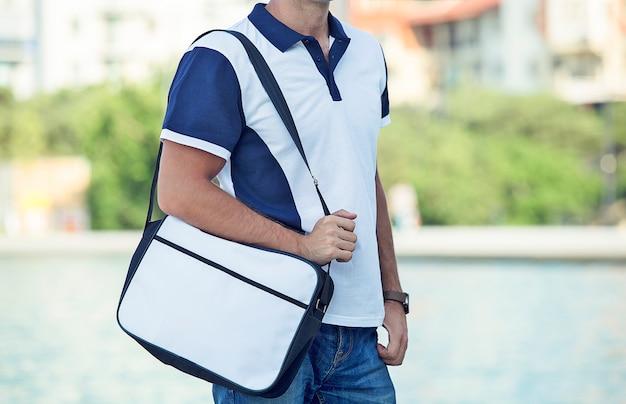 カジュアルなポロと小包を宣伝する男性のファッションモデル 無料写真