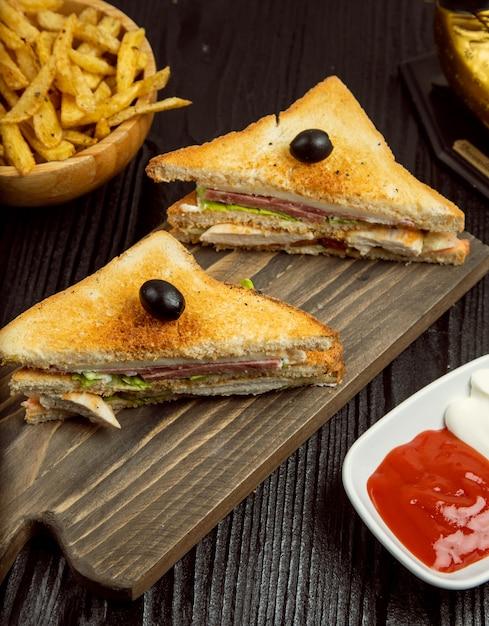 サラミ、ベーコン、フライドポテトのクラブサンドイッチ、ケチャップ、木の板のマヨネーズ添え。 無料写真